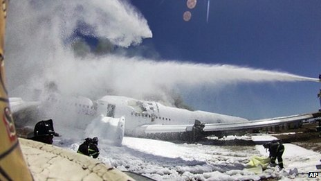This photo provided by the San Francisco Chronicle shows an image from the helmet-mounted video camera of a San Francisco fire battalion chief at the scene of the crash of Asiana Flight 214 shows a firefighter covering the body of passenger Ye Meng Yuan at San Francisco International Airport 6 July 2013