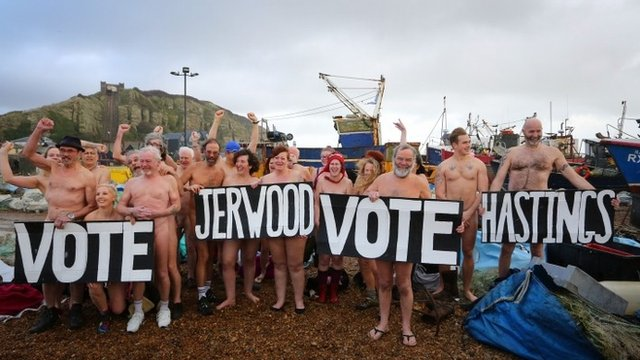 """Nude people on a beach with a sign that reads """"Vote Jerwood vote Hastings"""""""