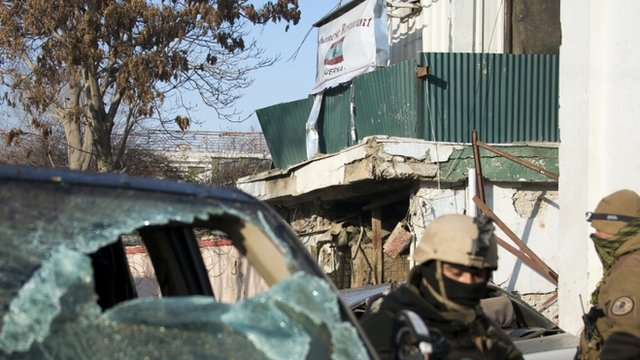 Afghan special forces soldiers stand guard next to the damaged entrance of a Lebanese restaurant that was attacked in Kabul