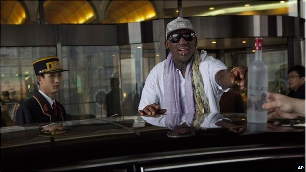 Dennis Rodman reaches to take a bottle of vodka from his bodyguard outside a Pyongyang hotel on Tuesday, January 7, 2014