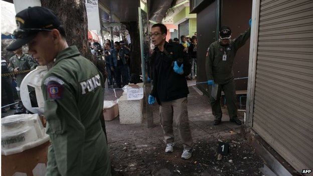 A Thai bomb squad unit examine the site of a blast at Victory monument in Bangkok on January 19