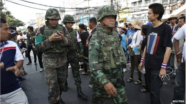 Thai military medics walk near the scene following an explosion at an anti-government protest camp at the Victory monument in central Bangkok January 19