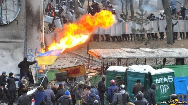 A protester sprays fire in the direction of the riot police during clashes in the centre of Kiev on January 20