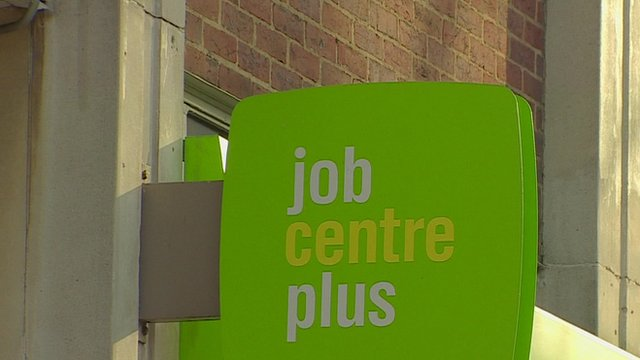 A green sign outside a London Job Centre reading 'job centre plus'