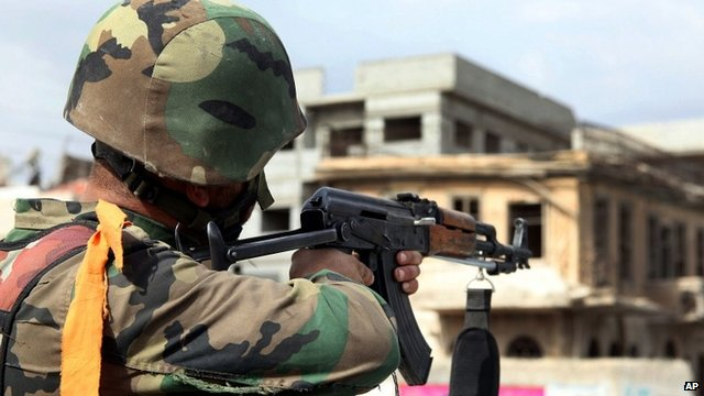 A Syrian army soldier takes his position, at a street in Sabina suburb