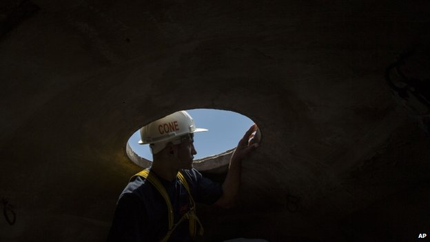 A worker looks outside from inside the head of the Christ Redeemer statue