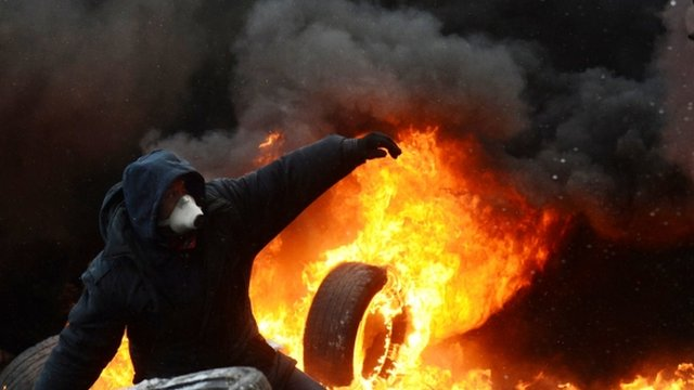 A Ukrainian demonstrator stands amid burning tyres during clashes in central Kiev
