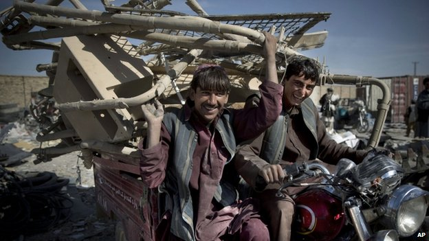 Afghan scrap collectors transport a load of destroyed US equipment from the departing military in Kandahar