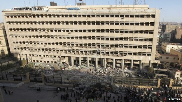 Police officers and people gather in front of the damaged Cairo Security Directorate building