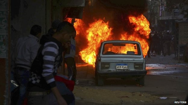 A vehicle is seen on fire during clashes between pro-Morsi protesters and police in eastern Cairo