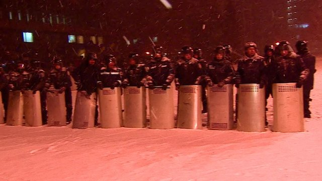 Riot police stand guard in the snow
