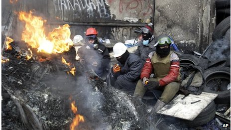 Anti-government protestors in Kiev rest behind a burning barricade in front of riot police