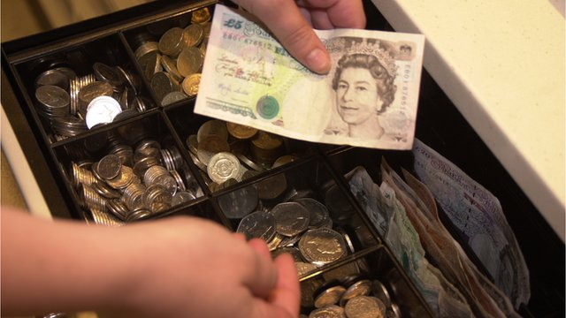 A supermarket checkout worker gives change