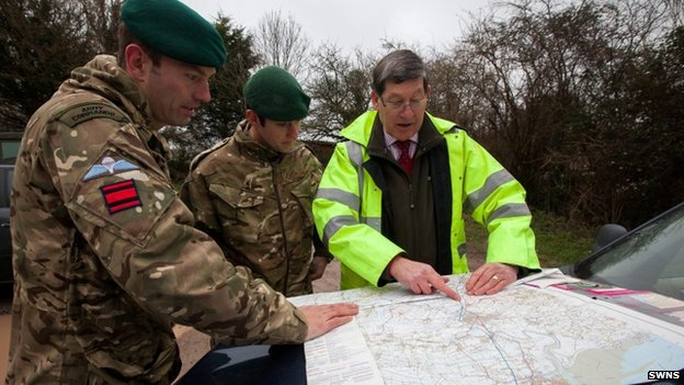 Two soldiers and a man in a high-visibility yellow jacket looking at a map placed on the bonnet of a car
