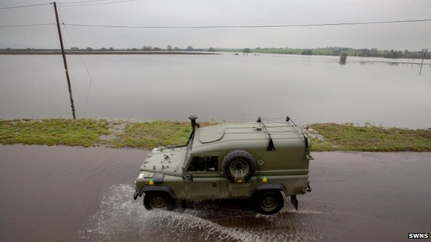 A military jeep drives along a flooded road