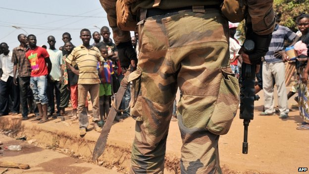 Local residents stand opposite a French soldier holding a machete confiscated from an anti-balaka combatant during a patrol in Bangui on 29 January 2014