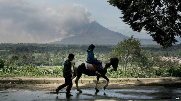A tourist rides a horse as Sinabung spews volcanic materials in Gundaling, January 21