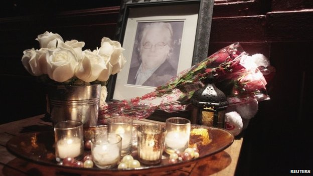 Flowers and candles are laid at a memorial for actor Philip Seymour Hoffman
