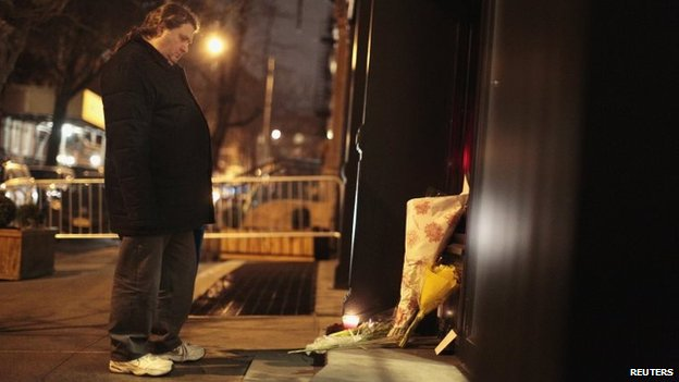 A man mourns in front of flowers placed in memory of actor Philip Seymour Hoffman