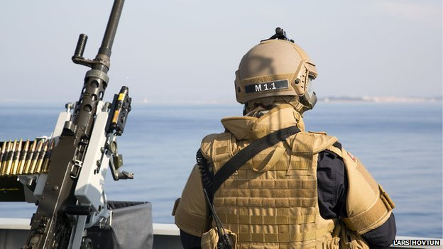 A Norwegian solder keeps watch, as chemical agents are loaded onto a nearby container ship in Latakia.