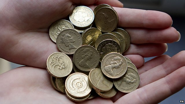 A person holds pound coins