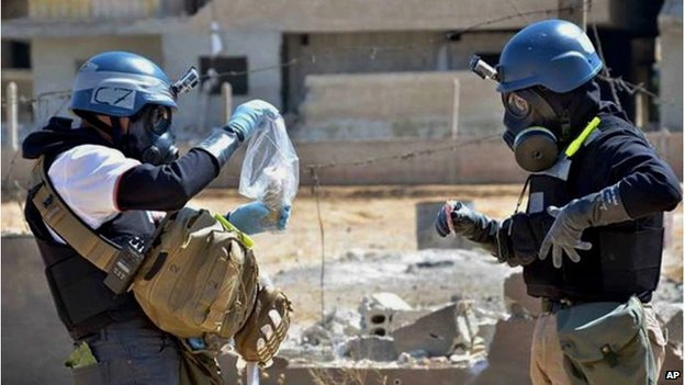 Investigators take samples of sand near a part of a missile that was suspected of carrying chemical agents, at a site near Damascus in August 2013