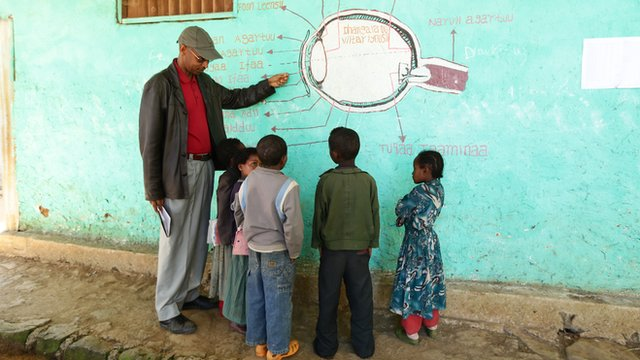 Man points to diagram of eye drawn on wall, children stand and watch