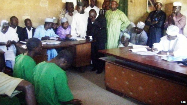 A picture taken on 22 January 2014 shows two suspected homosexuals in green prison uniforms (L) sitting before a judge in Bauchi, Nigeria