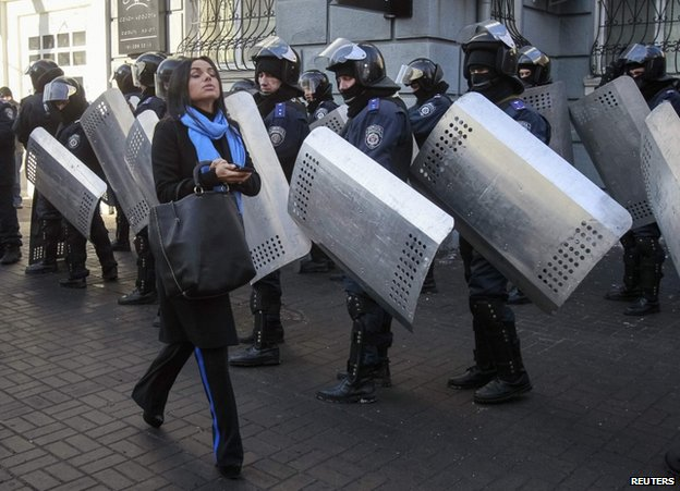A woman passes riot police in Kiev, 6 February