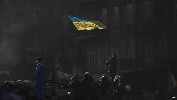 """An opposition supporter waves an Ukrainian flag on top of a barricade in a street heading to Kiev""""s Independence Square, the epicenter of the country""""s current unrest, Ukraine, Thursday, Feb. 6, 2014."""