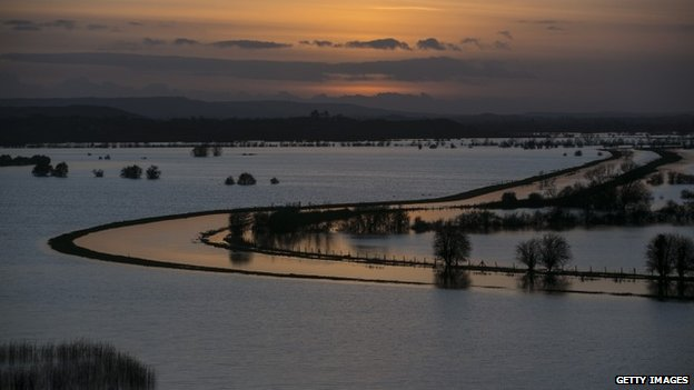 The sun sets over flooded fields surrounding the River Tone on the Somerset Levels.