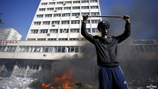 A protester stands near a fire set in front of a government building in Tuzla February 7, 2014