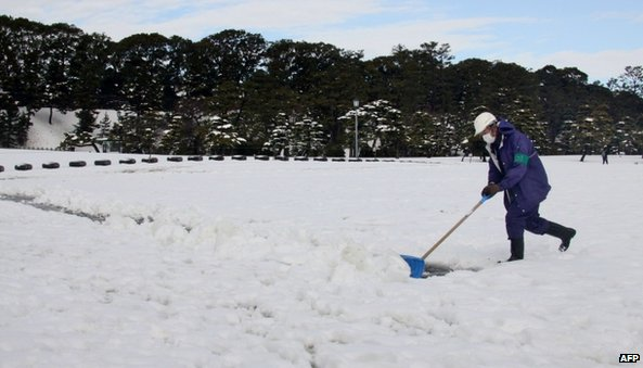 A man shovels snow to make a path at a park in Tokyo (9 February 2014)