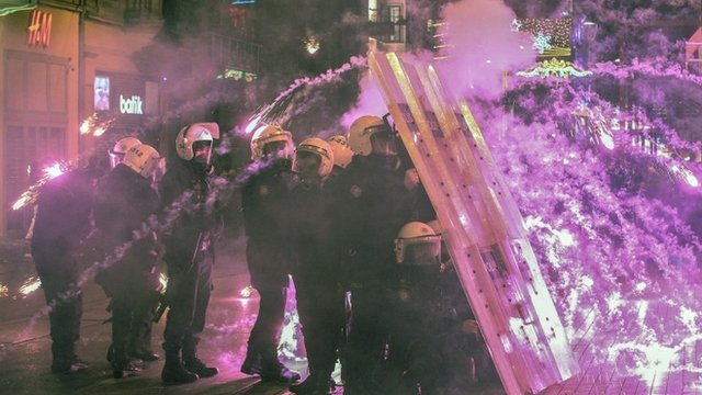 Riot police taking cover