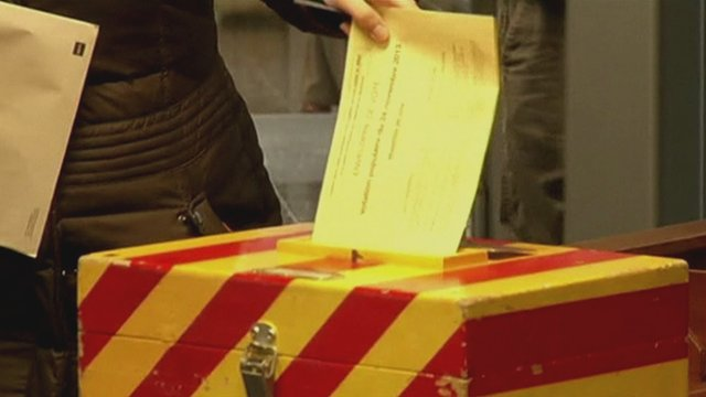 A Swiss voter puts her ballot in the ballot box