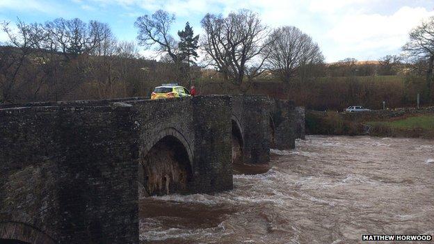 Police car on closed bridge over swollen river