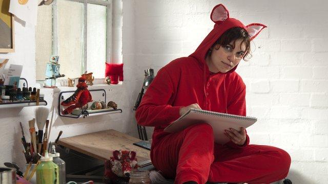 Woman dressed in red animal onesie