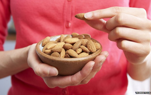 Woman holding bowl of almonds