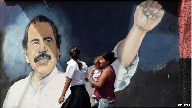 Nicaraguans walk past a Daniel Ortega mural on a wall
