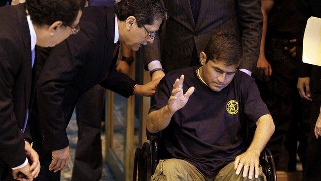 Jose Salvador Alvarenga gestures to El Salvador's Foreign Minister Jaime Miranda (centre) as media await him