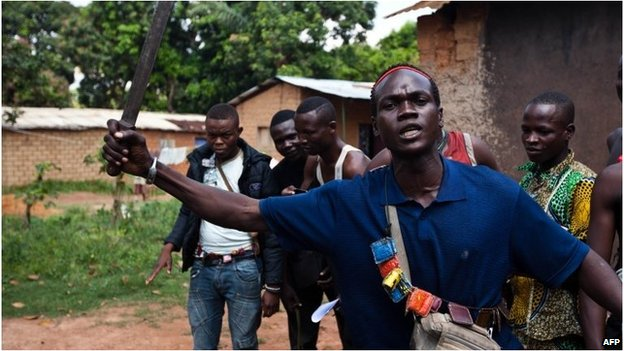 An Anti-Balaka fighter, member of a militia opposed to the Seleka rebel group, lifts up a machete threatening any Seleka that may attack in Bangui on December 14, 2013
