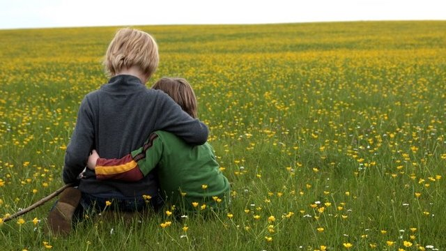 Children sitting in field - generic image