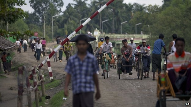 In this 14 September 2013 photo, Muslims travel past a road barrier next to a security checkpoint in Maungdaw, northern Rakhine state, Myanmar