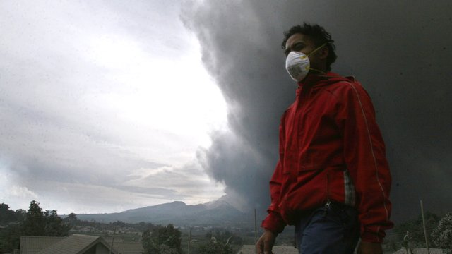 A resident of the Malang district in East Java evacuates as hot ash clouds erupt from Mount Kelud