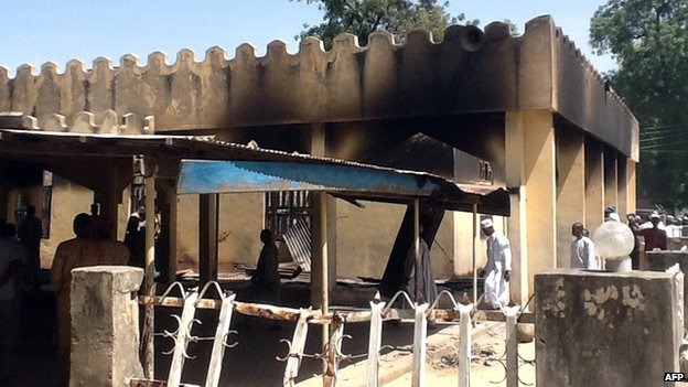 People walk around the damaged mosque in the village of Konduga, in north-eastern Nigeria, on 12 February 2014.