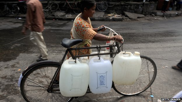 woman transporting water bottles on a bicycle, India