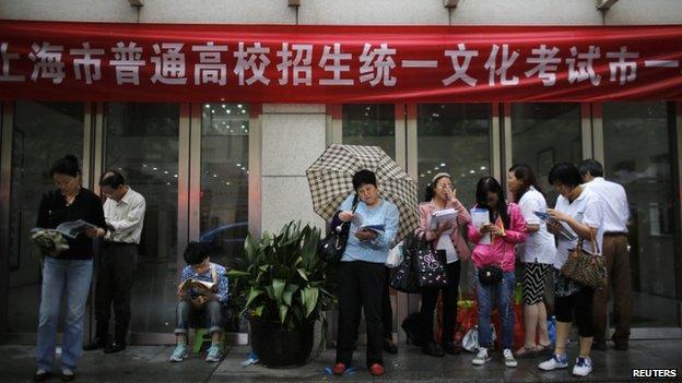 Parents wait for children outside a school in Shanghai