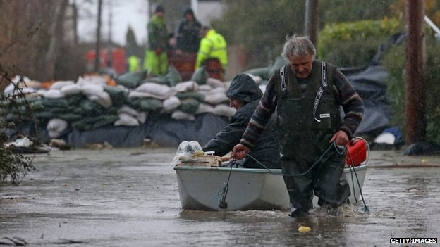 Moorland resident Derek Bristow pulls his wife Paula through flood water in his boat