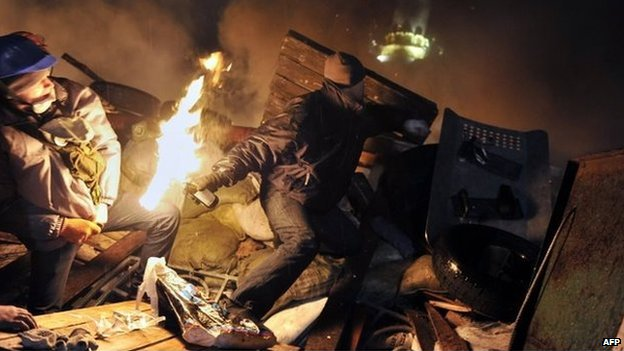 A protester hurls a petrol bomb towards police from the barricades at Independence Square in Kiev on Wednesday