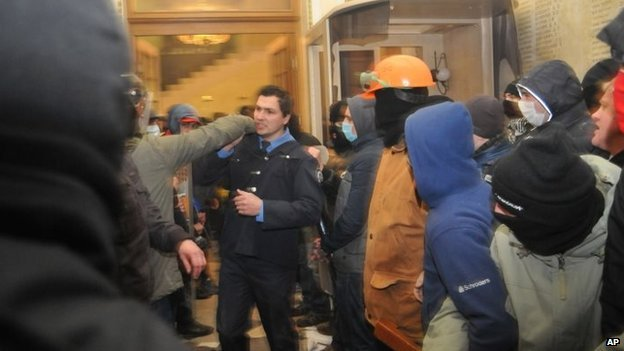 A policeman, centre, tries to stop Ukrainian protesters as they seize police headquarters in Lviv, western Ukraine, early on Wednesday